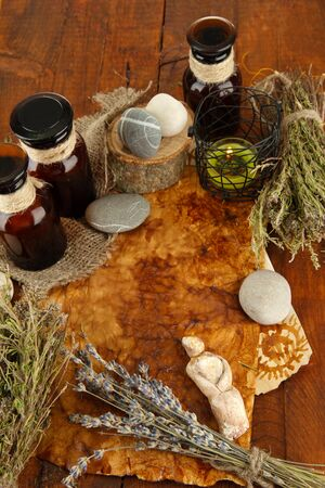 Composition with old papers, herbs, stones and bottles with symbols on wooden background photo