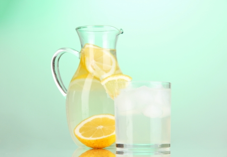 Lemonade in pitcher and glass on green background photo