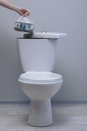 Hand hides money in toilet tank in a bathroom photo