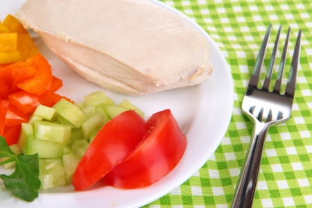 Boiled chicken breast on plate with vegetables close up photo
