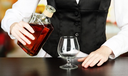 Barman hand with bottle of cognac  pouring drink into glass, on bright background photo