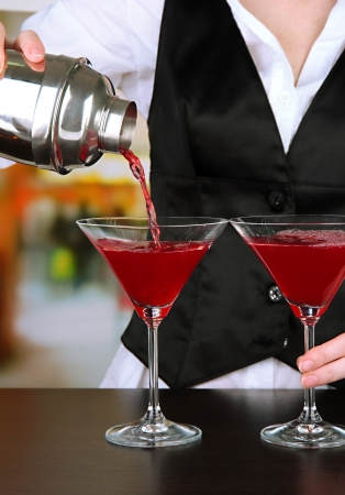 barmen: Barmen hand with shaker  pouring cocktail into glasses, on bright background