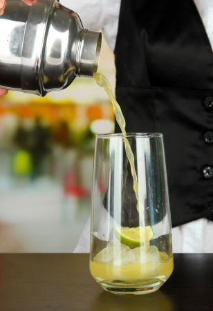 barmen: Barmen hand with shaker  pouring cocktail into glass, on bright background Stock Photo