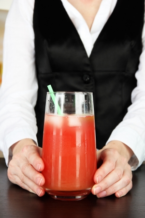 Barmen hand putting cocktail straw into glass, on bright background photo