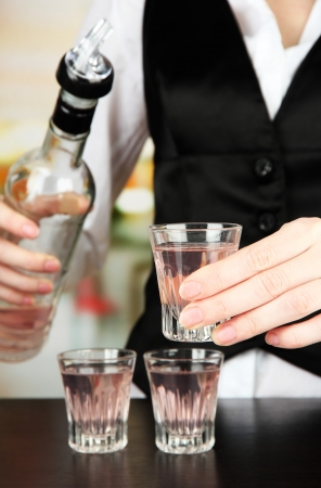 Barmen hand with bottle  pouring beverage into glasses, on bright background photo