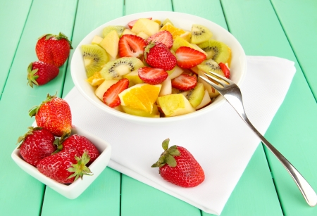 Useful fruit salad of fresh fruits and berries in bowl on napkin on wooden table close-up photo