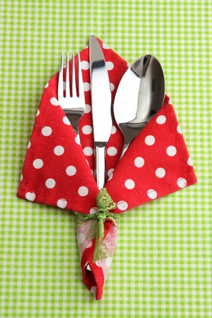 Fork spoon and knife in napkin on fabric checkered background photo