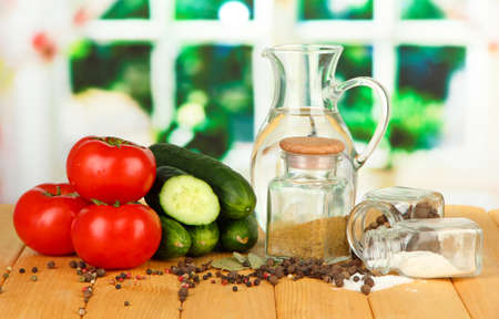 Tasty  fresh and canned cucumbers and red tomatoes, on wooden table on bright  background photo