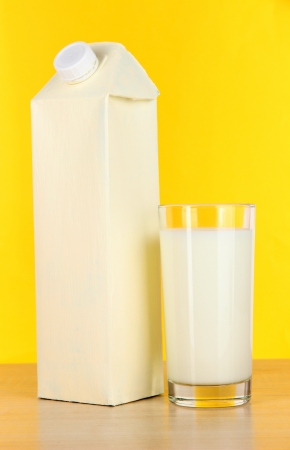 Milk pack on table on yellow background photo