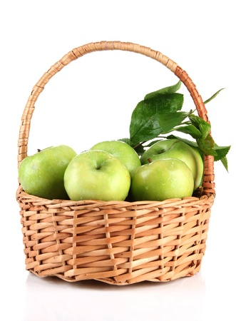 Juicy green apples with leaves in basket, isolated on white photo