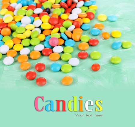 candy background: Colorful candies on green background