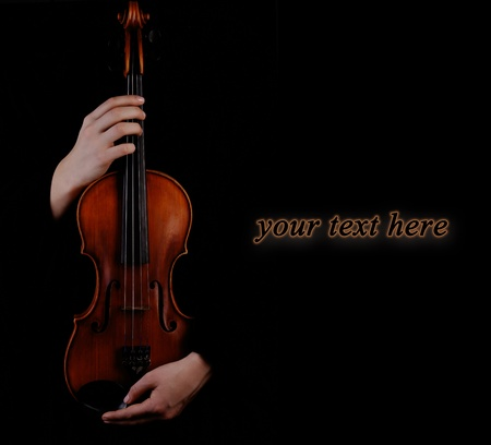 Violin in hands on black background photo