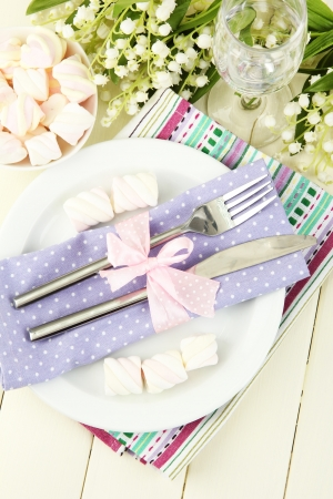 Table setting in violet and pink tones on color  wooden background photo