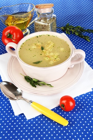 nourishing: Nourishing soup in pink pan on blue tablecloth close-up Stock Photo