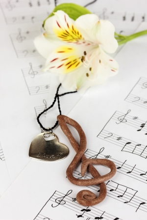 sheetmusic: Treble clef, pendant and flower on musical background