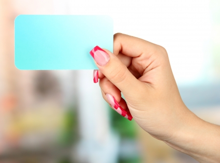 Female hand holding card, on bright background photo
