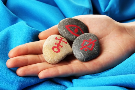Fortune telling  with symbols on stone in hand on blue fabric background Stock Photo - 19786273