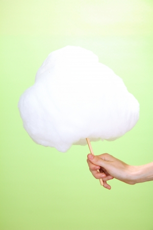 Hand holding stick with cotton candy, on color background photo