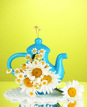 Beautiful bouquet chamomiles in teapot on color background photo