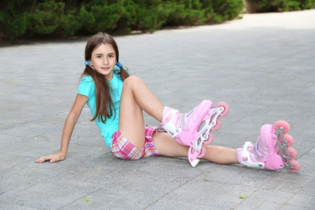 Little girl in roller skates at  park photo