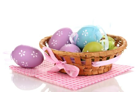 Colorful easter eggs in basket on napkin isolated on white photo