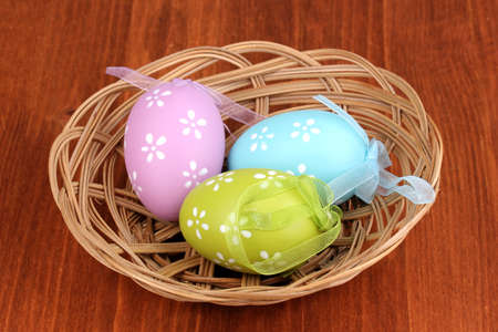 Colorful easter eggs in basket on wooden background photo