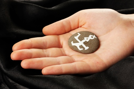 Fortune telling  with symbols on stone in hand on black fabric background Stock Photo - 19892555