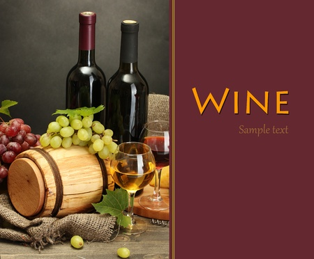 Still life of wine, grapes and cheese on wooden table on grey background photo