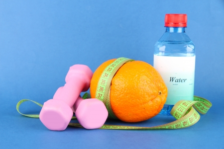 Orange with measuring tape, dumbbells and bottle of water, on color background photo