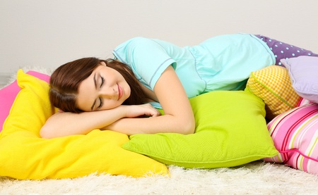 sleeping girl: Beautiful young girl with pillows in room Stock Photo