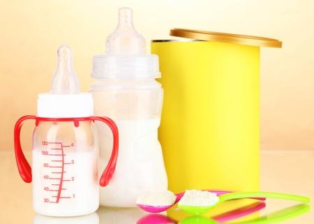 fondo para bebe: Botellas con leche y alimentos para beb?s en el fondo de color beige