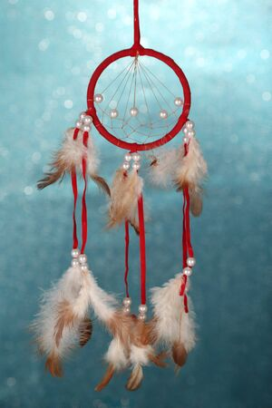 Beautiful dream catcher on blue background with lights photo