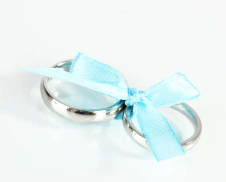 Wedding rings tied with ribbon isolated on white photo