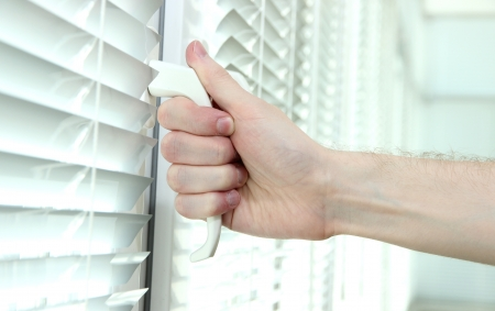 Someone opens metal-plastic window blinds closed Stock Photo - 19973986