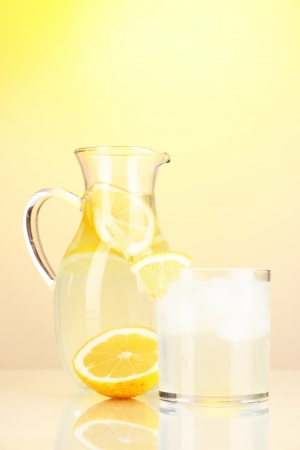 Lemonade in pitcher and glass on yellow background photo