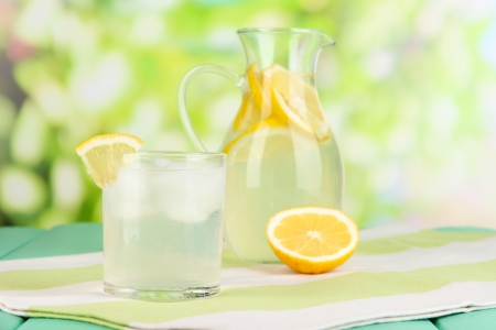 Citrus lemonade in pitcher and glasses on wooden table on natural background photo