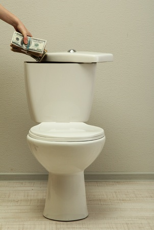Hand hides money in toilet tank in a bathroom Stock Photo - 19974021