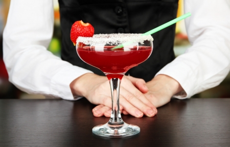 Barmen hand with shaker  pouring cocktail into glass, on close up photo