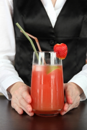barmen: Barmen hand putting cocktail straw into glass, on bright background