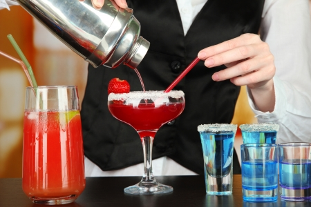 cocktail glasses: Barmen hand with shaker  pouring cocktail into glass, on bright background Stock Photo