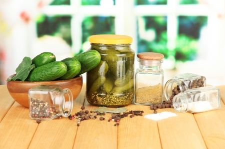 Tasty  fresh and canned cucumbers, on wooden table on bright  background photo