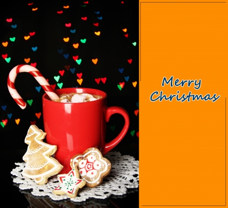 Cup of coffee with holiday candy on Christmas lights background photo