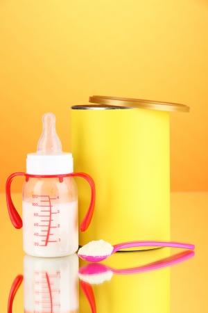 fondo para bebe: Botella con la leche y los alimentos para beb?s en el fondo de color naranja