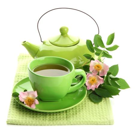 plantas medicinales: Taza y tetera de té de hierbas con el hip flores rosa, aislado en blanco