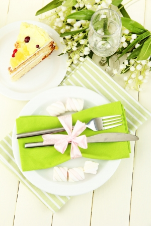 background settings: Table setting in white and green tones on color  wooden background