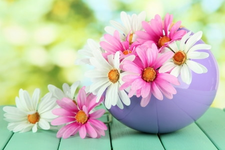 Pot with flowers on a wooden table on the nature background photo