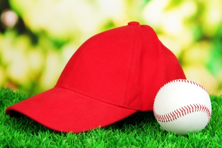 peaked: Red peaked cap on grass on natural background Stock Photo