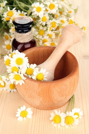 Essential oil and chamomile flowers in mortar on wooden table photo