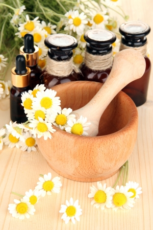 alternative medicine: Essential oil and chamomile flowers in mortar on wooden table Stock Photo