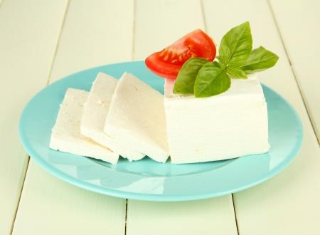 queso blanco: Queso de leche de oveja, con albahaca y tomate en el fondo de madera de color Foto de archivo